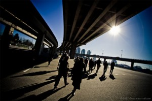 Pedestrians walk across the concrete field that lies underneath the viaducts.
