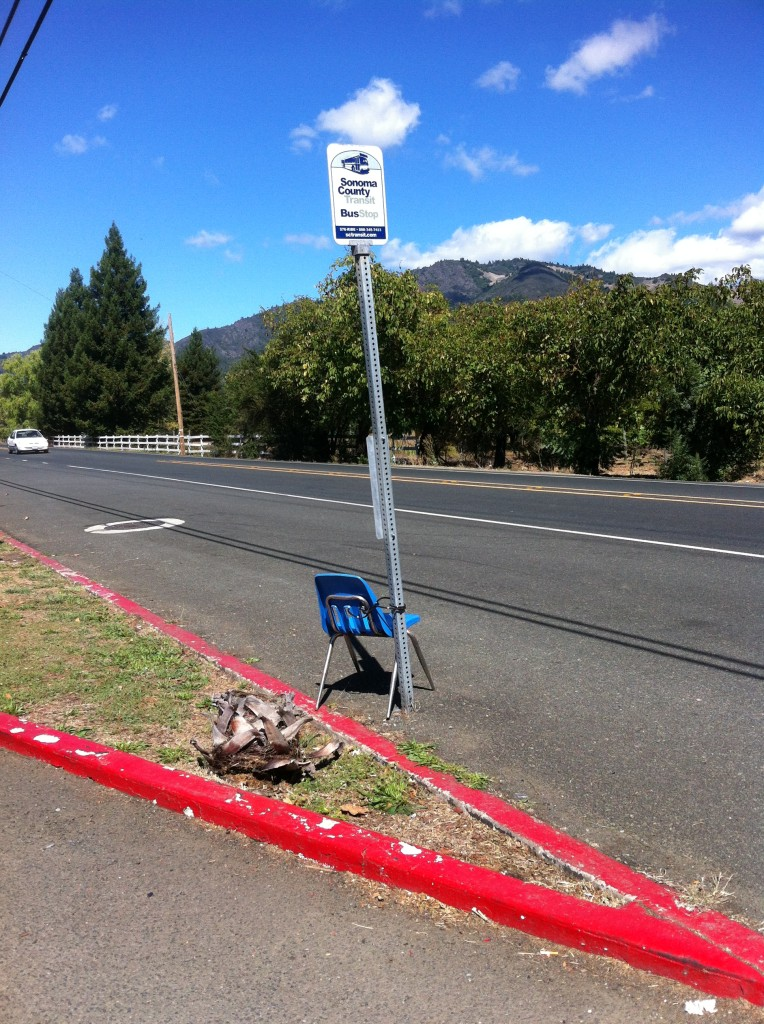 Plastic chair chained to a bus stop pole on Sonoma Highway in Kenwood, CA