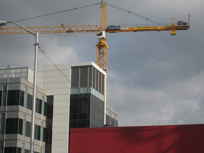 A crane with Vulcan's name stands above a construction site, South Lake Union, Seattle, Washington