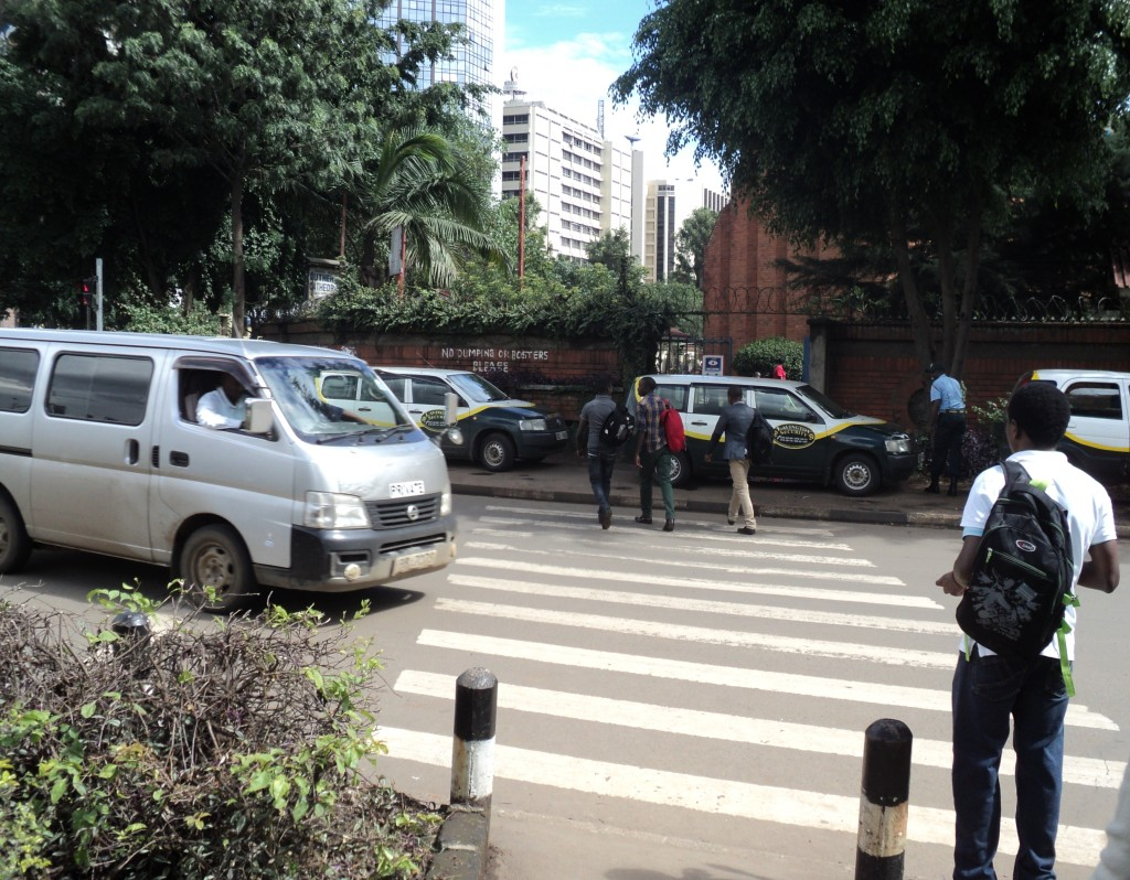 Vehicles stop to allow pedestrians to cross the road at a zebra crossing