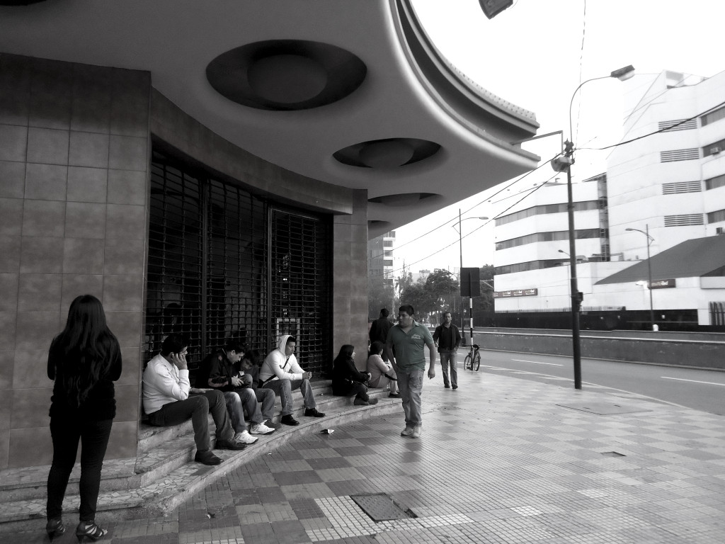 People waiting outside a former cinema, now a temple, in Lima, Peru
