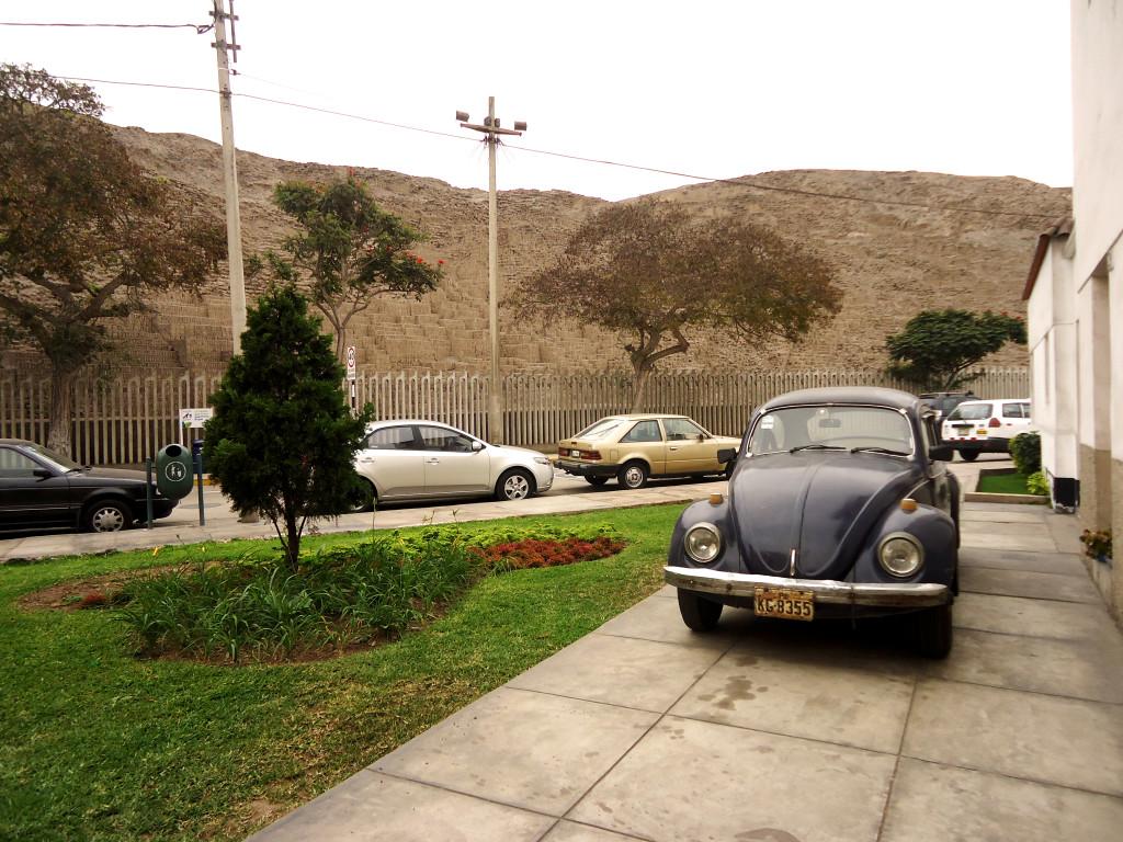 A Volkswagen Beetle sits among the fancier cars of the Pucllana neighborhood, Lima