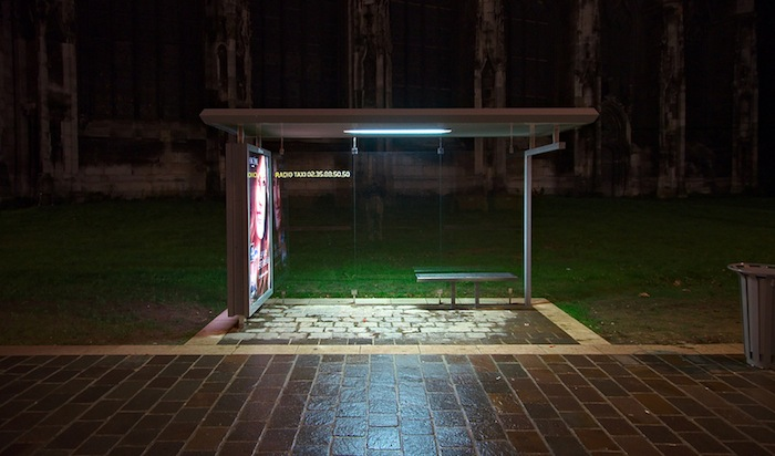 A bus stop at night.