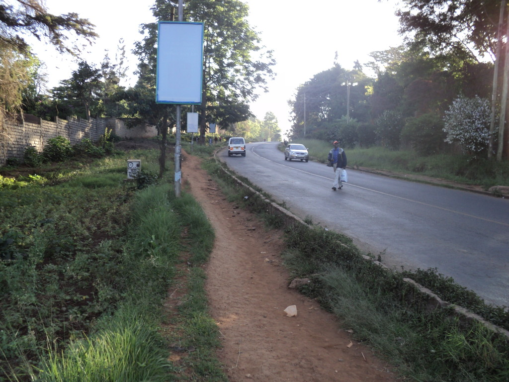 A Nairobi Citizen crosses the road towards a dusty pavement