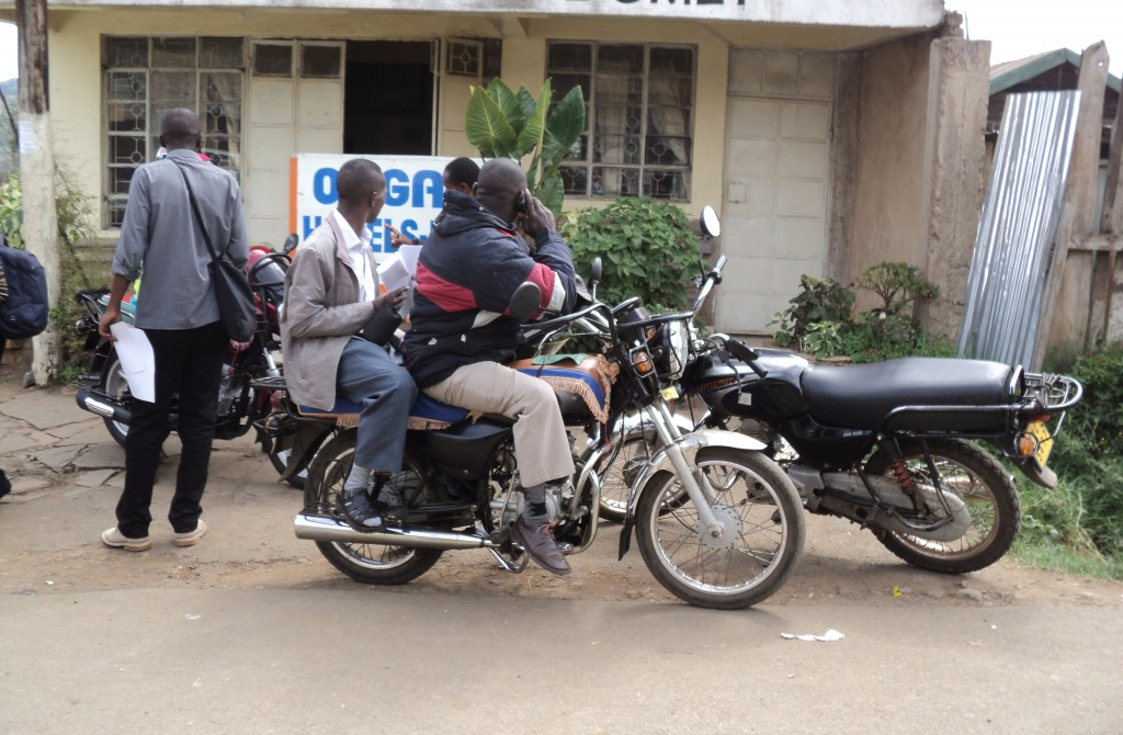 A man boards a motorcycle taxi with neither a helmet nor reflective clothing, Nairobi, Kenya