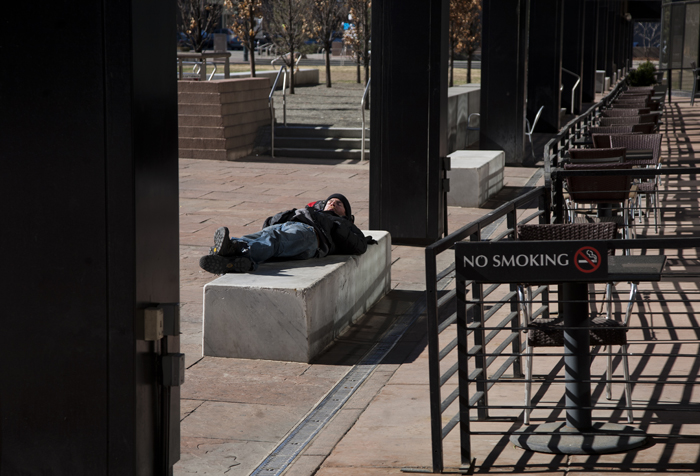 A man sleeps in a public plaza on the 16th Street Mall in Denver, Colorado