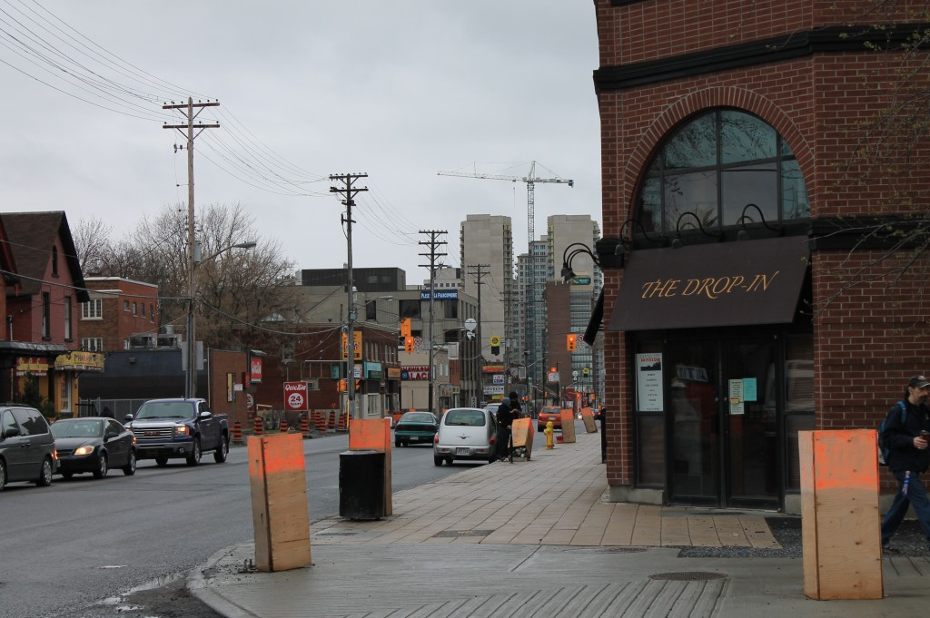 View along Rideau Street with interrupted sidewalks, utility poles, and mismatching buildings