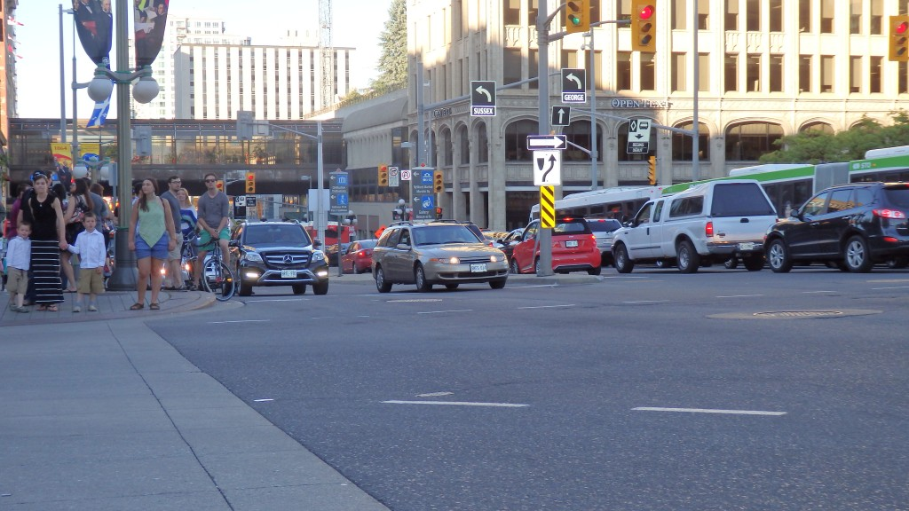 Bikers on the edge of traffic on busy road with no bike lanes, Ottawa, Canada