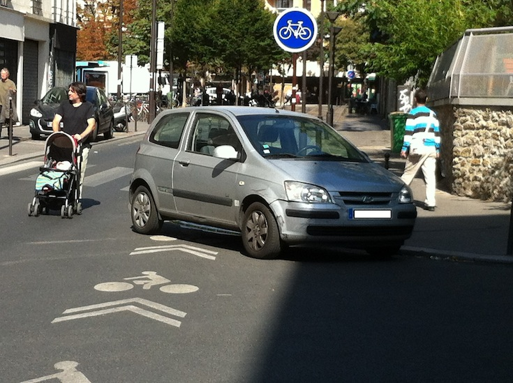 A parked car obstructs a bicycle lane in the streets of Paris, France. Credit: Olivier Razemon.
