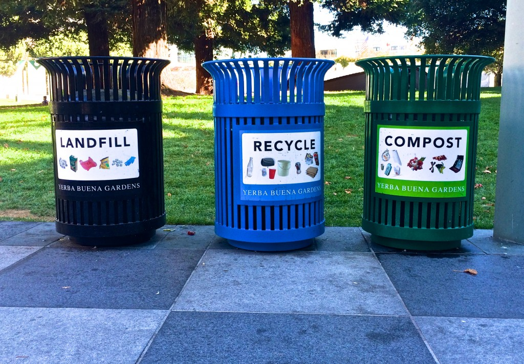 """Zero-waste bins, San Francisco, California. Black bin on left marked """"Landfill."""" Blue bin in center marked """"Recycle,"""" and green bin on right marked """"Compost."""""""