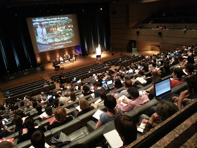 Ampithéâtre in Montpellier, an existing conference space. Seats are filled with people watching a presentation about the national library of Copenhagen
