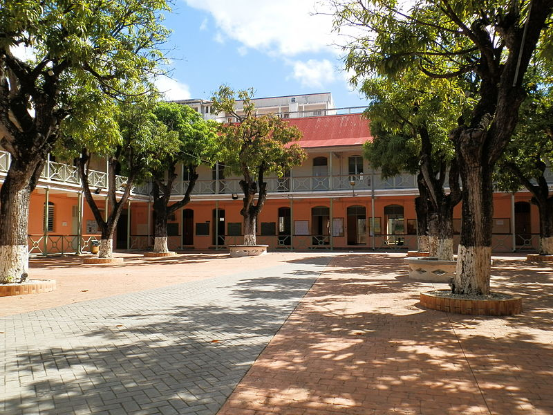 Gerville-Reache High School in Guadeloupe, Carribbean. Photo shows the school's courtyard that is lined with trees.  The building's outdoor hallways look out over the courtyard.