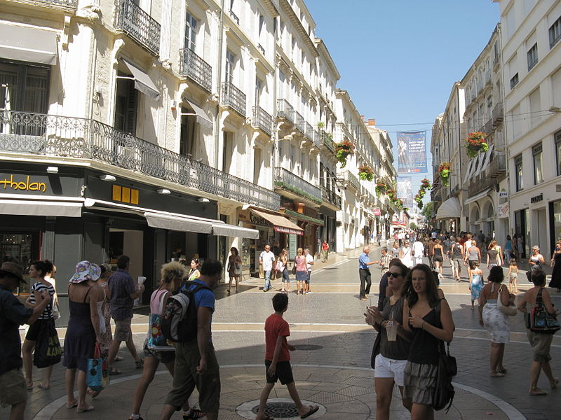 View up Rue de la Loge, the most important shopping street in Montpellier, France. The street is relatively crowded with people and is lined with businesses.