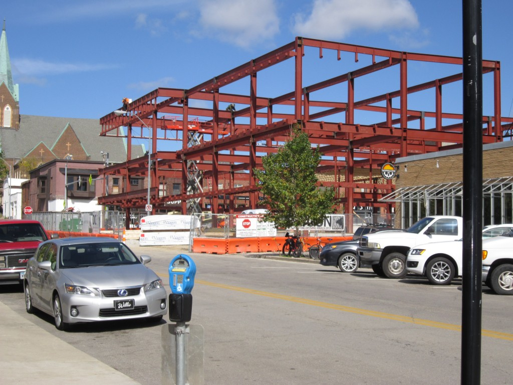 Mixed-use development in East Village being constructed.  Red metal framing for building can be seen. Des Moines, Iowa