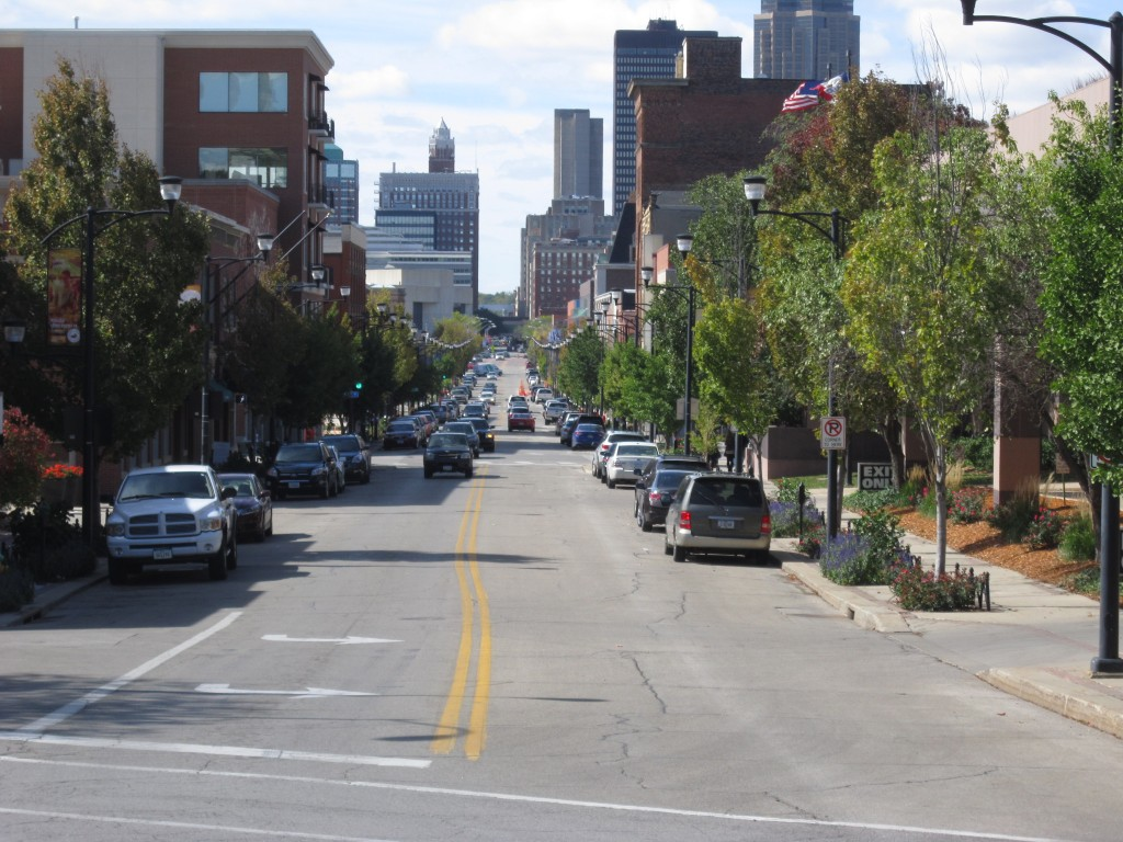 View down a street of East Village in Des Moines, Iowa showing trees along the sides of the street and city skyscrapers in the background