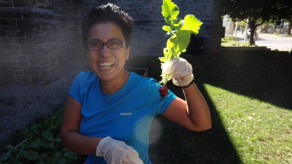 Urban Shades volunteer holding up radish, Ottawa, Canada