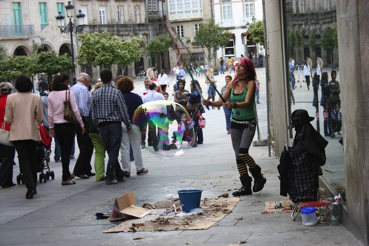 Pedestrians and a street performer in Pontevedra, Spain