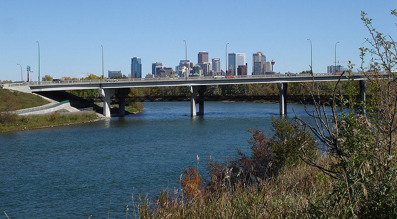 Bow River overlooking city of Calgary, Canada.  Grassy bank of river in foreground, leading to a bridge, beyond which is the skyline of Calgary