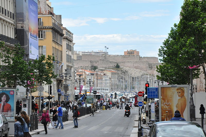 Photo is of La Canebière, a large street in Marseille, France.  There are buildings lining the street on the left side of the photo. Crowds of people fill the sidewalk.  The right hand side shows parked cars and a tree next to the street. At the end of the street, in the middle of the photo, is a port.  The masts of boats stick up. A 17th century fort, Fort Saint Nicholas, occupies the middle of the background.