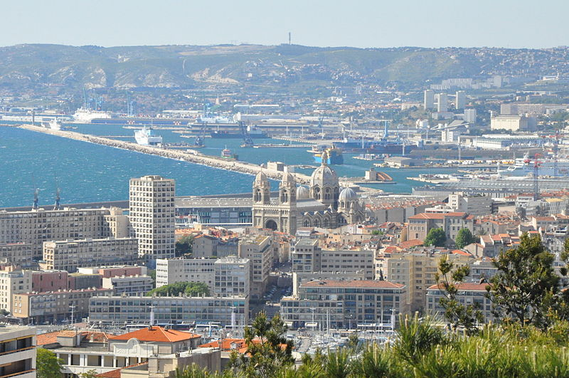 View of Marseille, France shows low-income housing buildings in foreground with the rest of the city spread behind, the sea visible on the left