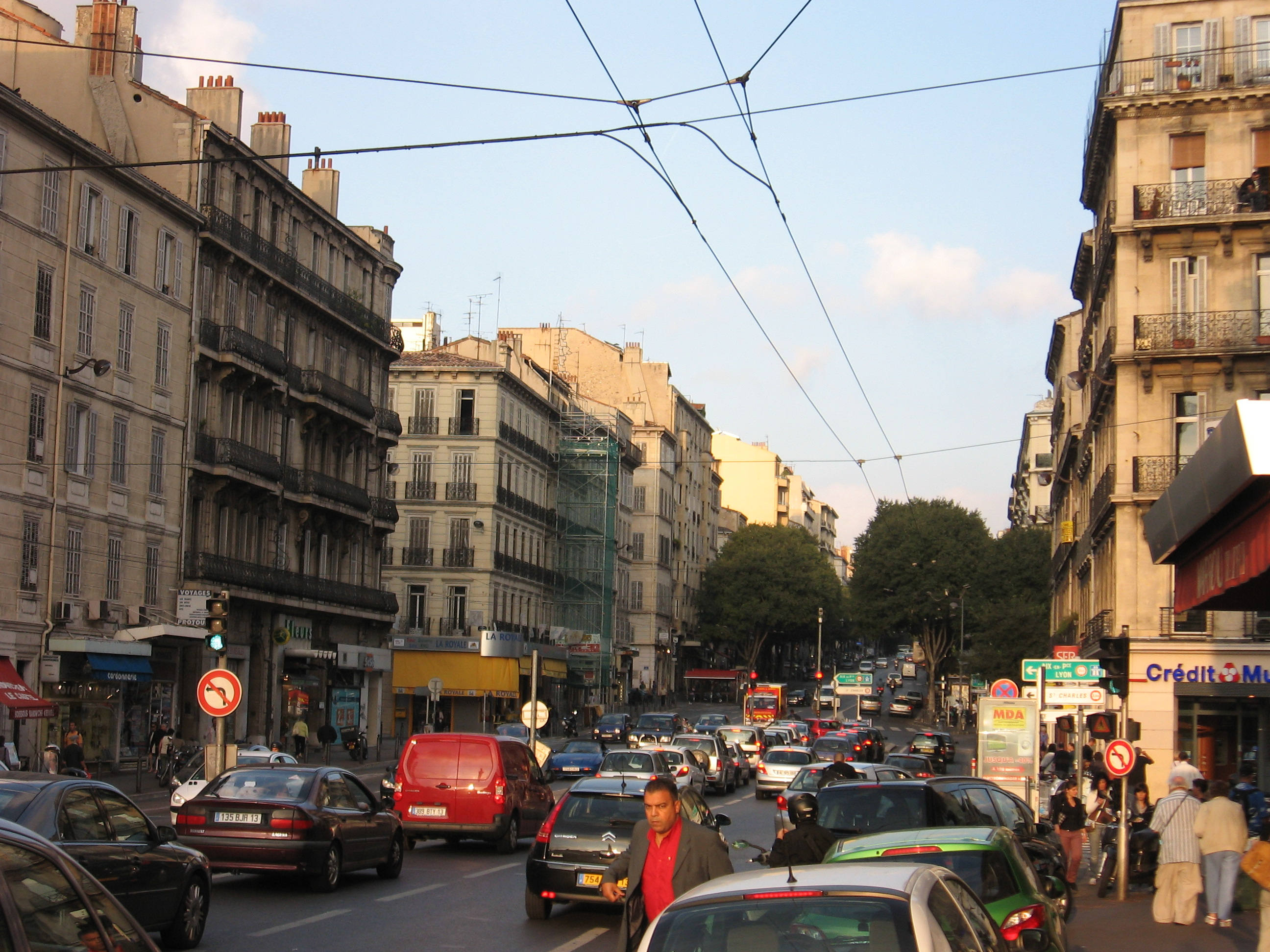 Boulevard Baille in Marseille, France shows City's Congestion. The photo depicts a major street in Marseille that is filled with cars.  Cars have even attempted to park halfway up the sidewalk on the right side of the photo. A man attempts to cross the street in-between the parked cars.