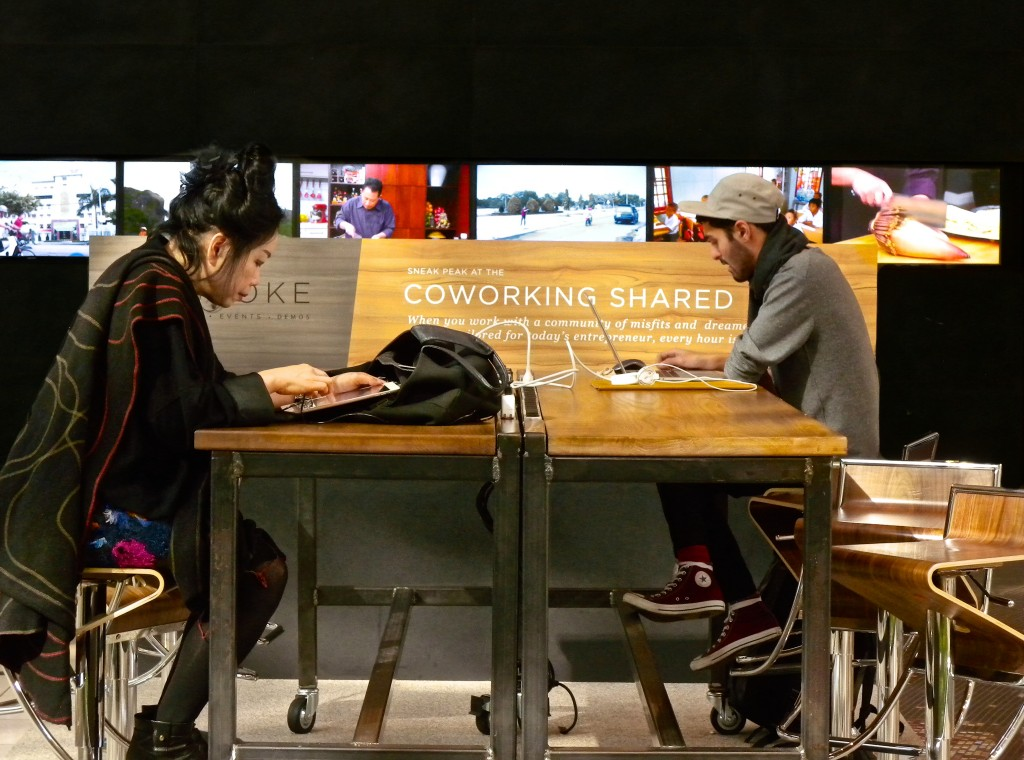 Westfield Coworking Space, San Francisco, California. Two people work at open tables across from each other.