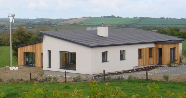 Passive house in  Galway Ireland. Modern house in center of photo, rolling green hills in background and small wind turbine to the left of the house