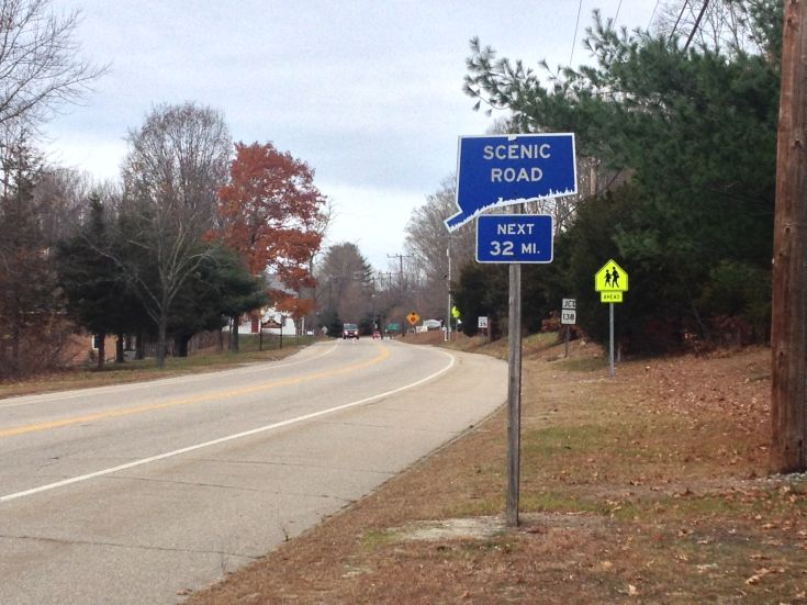 "First Northbound Sign in Lisbon, Connecticut.  Blue sign reads ""Scenic Road Next 32 MI."" Fall trees line the road."