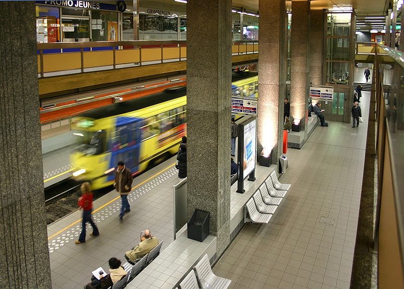 De Brouckère Metro Station, Brussels, Belgium. Platform seen from above. Outdated decor, concrete poles and benches in center. Metro train zooming by on the left