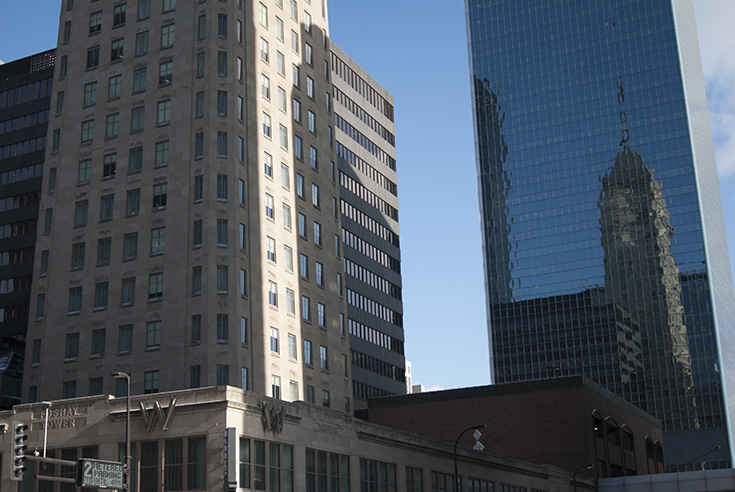 In the lower portion of the photograph you can see the entryway into the Foshay Tower in Minneapolis, Minnesota. The tower rises up and out of the frame on the left, while the entirety of the building can be seen in the reflection of the blue glass facade of the Campbell Mithun Tower on the right.