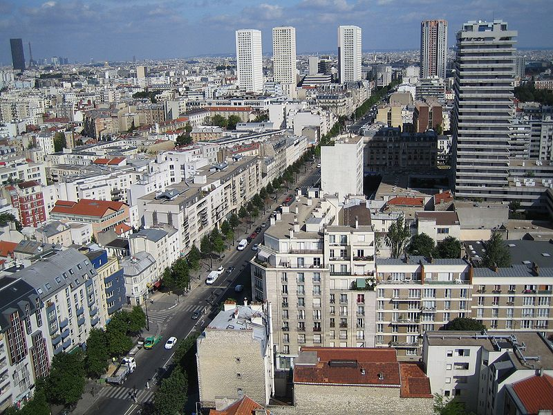 Aerial view of Avenue d'Italie in Paris, France, showing many low-rise apartments in foreground and high-rises in backgrond