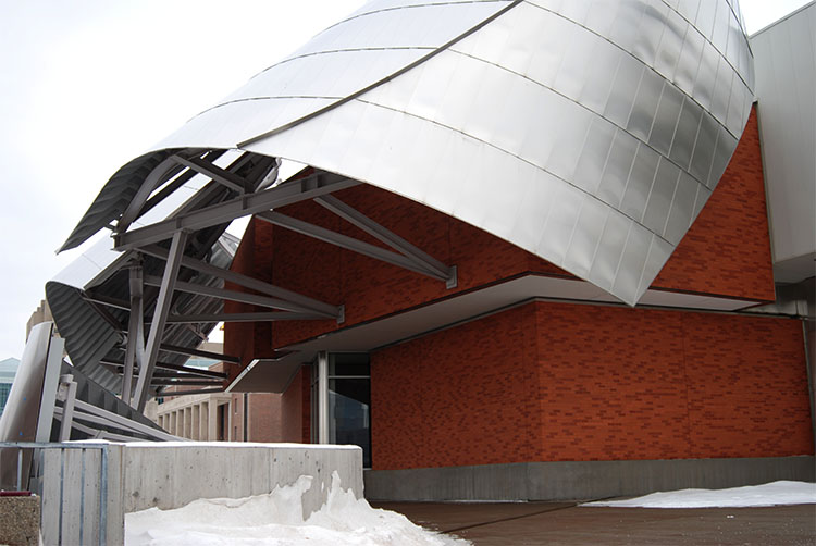 A close-up of the Weisman Art Museum's North-facing facade. The mixture of stainless steel and brick is beautifully crafted. In the distance, the University of Minnesota - Twin Cities Coffman Memorial Union is seen.