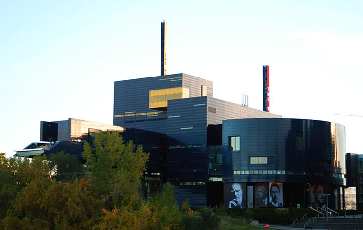 "The Guthrie Theater in Minneapolis, Minnesota features a deep blue colored, stainless steel facade. On the left, emerging through the trees, is the ""Endless Bridge"", a 178-foot cantilever which protrudes from the building."
