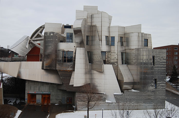 The West-facing facade of the Weisman Art Museum. On the upper left hand side of the building you can see some of the brick portion of the facade peaking through. On the lower left of the building, the museum's parking garage entrance and exit is shown.