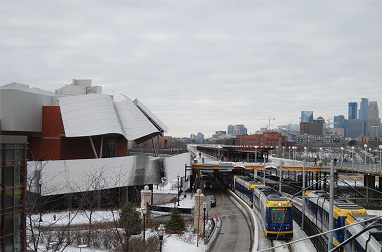 The Weisman Art Museum's East-facing facade. The Minneapolis skyline stands tall in the distance, while two light-rail trains pass each other on the edge of the Washington Avenue Bridge over the Mississippi River.
