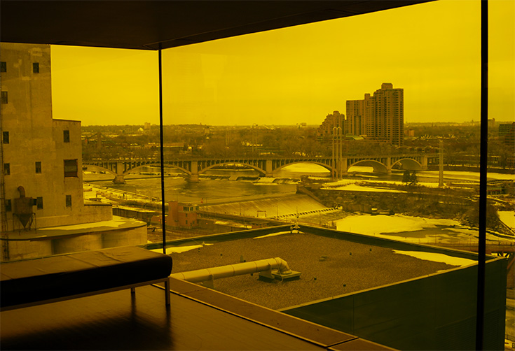 The Dowling Studio Lounge features floor-to-ceiling yellow-tinted windows, giving incredible views of the surrounding landscape. As seen here, spectacular views of the Mississippi River and St. Anthony Falls are given.