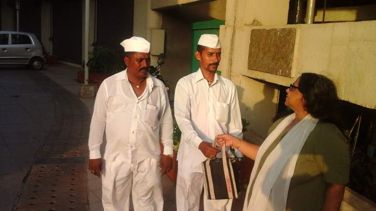 Dabbawallas handing recieving a 'dabba' (luncbox) from a patron, Mumbai, India