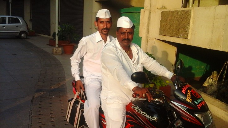 Dabbawallas on a motorbike. Dabbawallas typically use bicycles, however do use simple motor-vehicles such as motorbikes for longer distances.