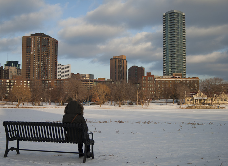 A Loring Park visitor is seen enjoying the view of a frozen Loring Lake with a skyline of apartment buildings beyond, predominantly the towering LPM Apartments on the right side of the image.