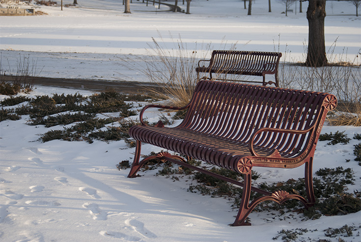 Two red benches reflect the warm light from the setting sun in Loring Park, located in Minneapolis, Minnesota.