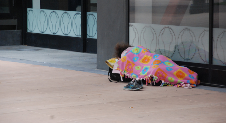 Homeless person sleeping on the main street pedestrian mall in Downtown Riverside, CA