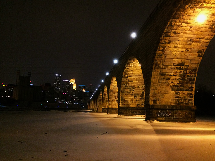The Stone Arch Bridge reaches towards downtown Minneapolis in the  night in the heart of winter. The frozen Mississippi River receives a glow from the indirect lighting located under the Bridge, illuminating its arches.