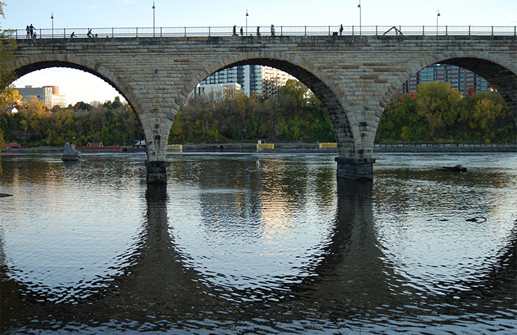 The historic Stone Arch Bridge in Minneapolis, Minnesota spans across the Mississippi River beautifully, as seen here with its crisp reflection on the water.