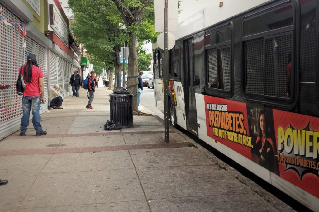 Student waiting by broken down bus, Baltimore City, MD