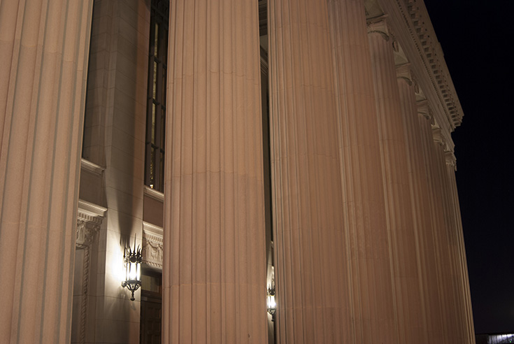 The Northrup Auditorium's front facade is illuminated at night, including its spectacular ionic colonnade.