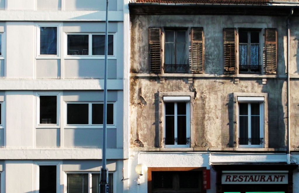 Facade of deteriorating  apartment building above a restaurant, France