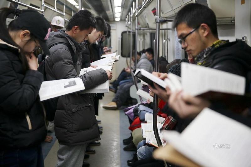 Riders reading in the crowded Beijing subway, Beijing, China