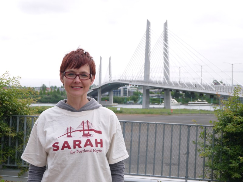 Sarah Iannarone standing in front of Tilikum Crossing, the largest bridge in the US that allows access for pedestrians, transit and cyclists but no personal automobiles.