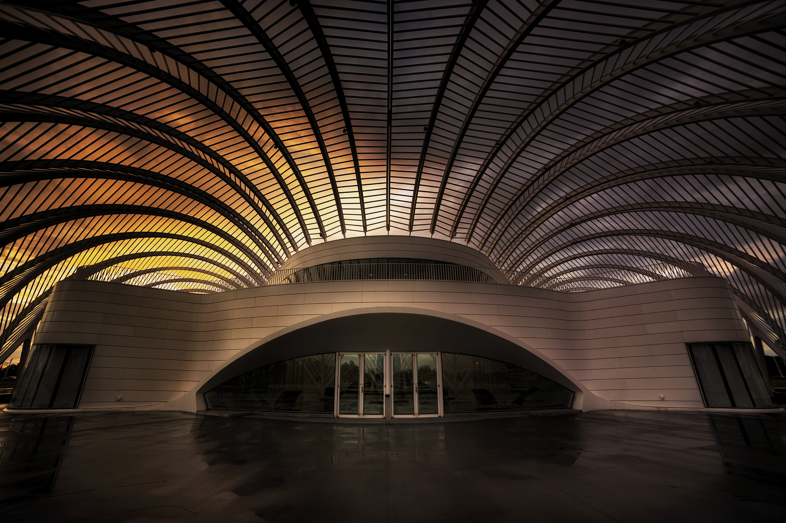 Image of the outside of Florida Polytechnic University's futuristic main enterance at sunset