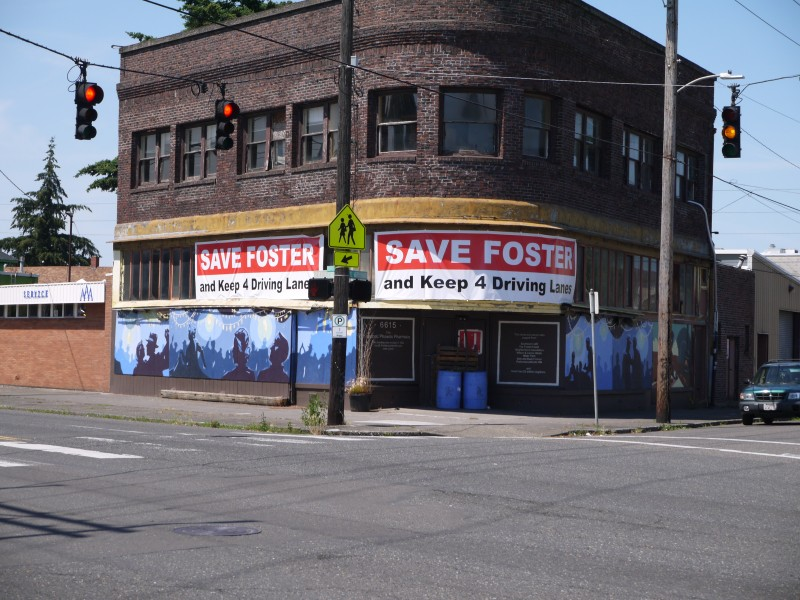"A pair of signs hang on a building overlooking an intersection of Foster Road and 67th Avenue. The signs read ""Save Foster and Keep 4 Driving Lanes"""